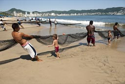 Boys try to help pill the net in, Acapulco, fishing on beach with nets..