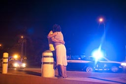 Hugging at night. Police blue light in back, Mexico, Acapulco.