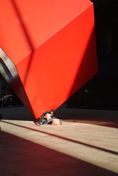 In NY, sun and red cube, financial district.