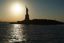 Liberty island and statue, silhouette against sun.