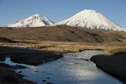 Volcanoes Pomerape and Parinacota over a blue stream high up, northern Chile.