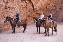 # young female tourists on horses in garganta de diablo, San Pedro Atacama.