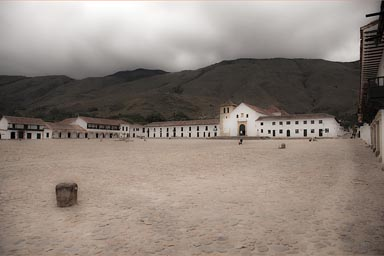 Look at Villa de Leyva main cobbled stone square, empty and cloudy in morning, Colombia.