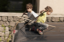 Twin boys play on top of van.