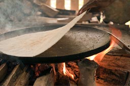 Yuca bread peals of iron plate on wood fire, Amazon basin, Ecuador.
