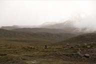 Chimborazo in a misty distance. Men rides a horse in front.
