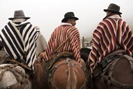 On horsebacks, in ponchos, Indigenas horses and bulls fiesta, Salinas de Guaranda, Ecuador.
