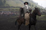 Man on horse, black and white poncho and llama wool. Salinas de Guaranda.