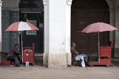 Shoe cleaners wait for clients in Cuenca under arcades. Ecuador.