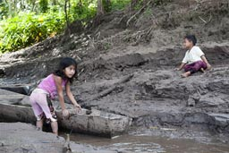 A canoe, muddy banks, the River Huallaga, children play.