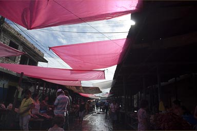 Red tarp against sun, covering market streets in Iquitos, Peru.