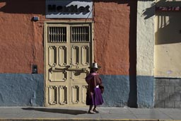 Indigenous woman in dress and hat walks a morning lighted street in Cajamarca, Peru.