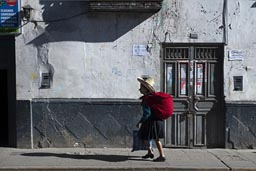 Woman and red pack walk by in morning sun, in front of white house and wooden door, Cajamarca, Peru.