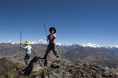 My boys and sticks on top of some rock, in the background, snow capped Cordillera Blanca mountains, Peru.