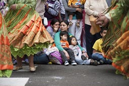 Family and children watch Independence Day parade from the ground. Lima, Peru.