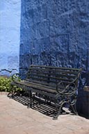 Blue wall, black iron bench, gardens in Santa Catalina convent, Arequipa.