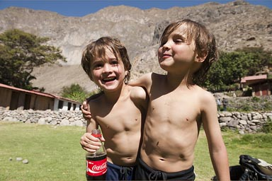Canyon walls of Colca in back, the boys Daniel and David in Oasis de Sangalle with a Coke bottle, Peru.