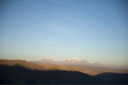 We drive high plateau in Andes and sun sets, in distance Chachani and Misti, volcanoes, Peru.