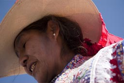 She offers a fermented drink of Mais/Corn, Huambo, bull fight, Quechua woman with hat. Peru.