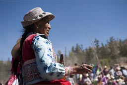 She splashed beer, old Indigenous woman on bull fight, Huambo, Peru,