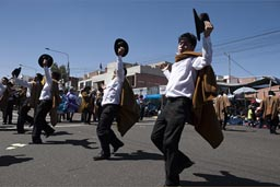 Black pants, white shirts, raise hats, men dance down la Avenida de Independencia,  Arequipa Day, Peru.