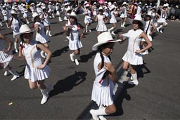 Girls dressed white, short skirts and white hats, Arequipa Day parade, Peru.