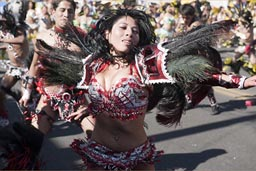 Dancer in red decorated bikini and feathers, extatic dance, Arequipa Day.