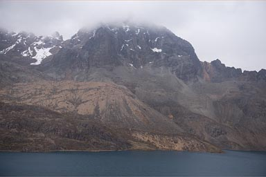 East of Lima 4,700m, a lake and snowy Andean mountains, clouds.
